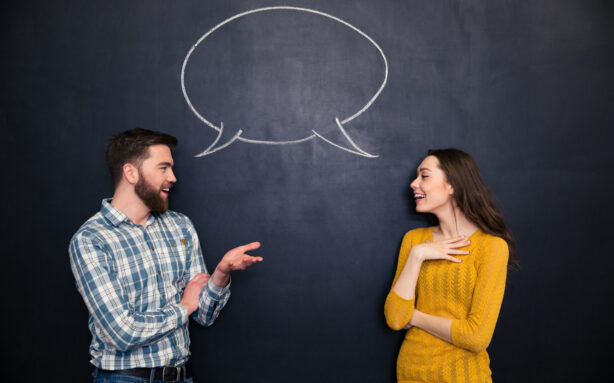 Happy young couple talking over chalkboard background with drawn empty dialogue