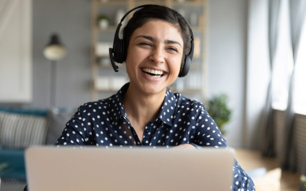 Cheerful indian woman wear headset laugh using laptop video stream conference call teach online, happy ethnic girl student gamer tutor have fun watch webinar web cam education entertainment concept